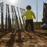 Header Image - child with a row of bats against a fence