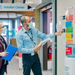 A woman and a man checking a bulletin board
